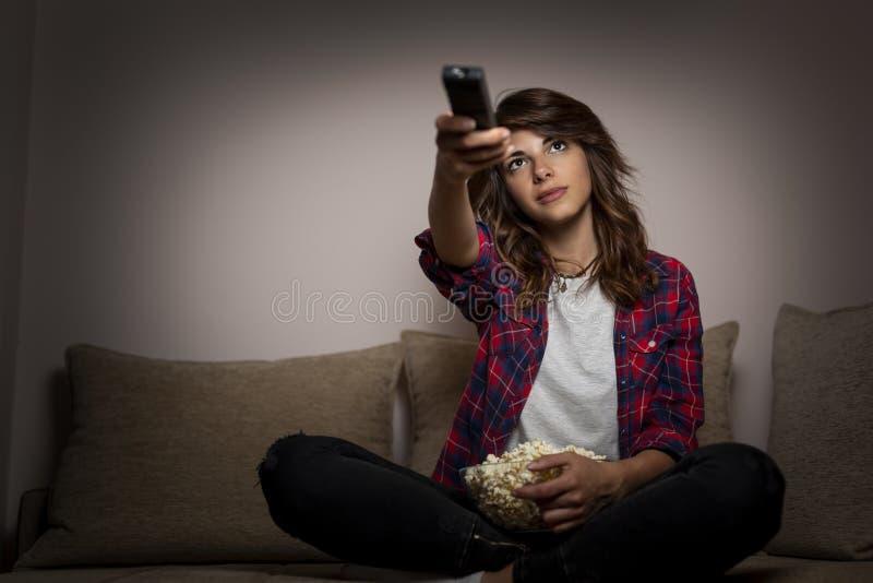 Vrouw die TVkanalen verandert royalty-vrije stock afbeeldingen