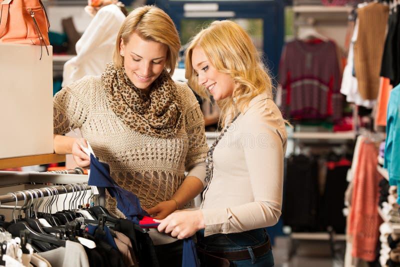 Vrouw die - Twee meisjes in een choo van de klerenwinkel winkelen royalty-vrije stock foto