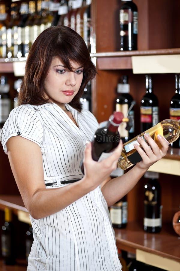 Vrouw die twee wijnen vergelijkt stock afbeeldingen