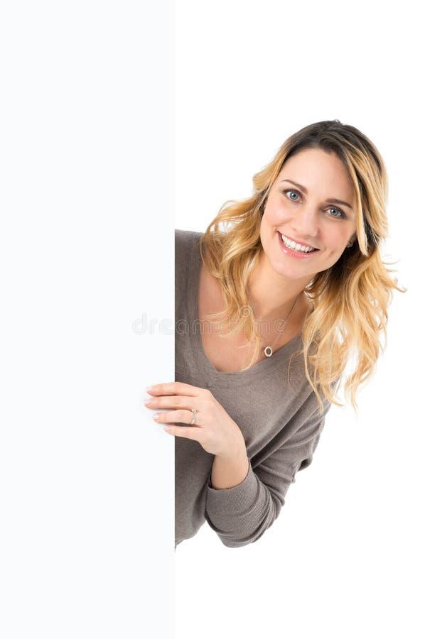 Vrouw die uit achter Aanplakbiljet komen royalty-vrije stock afbeeldingen