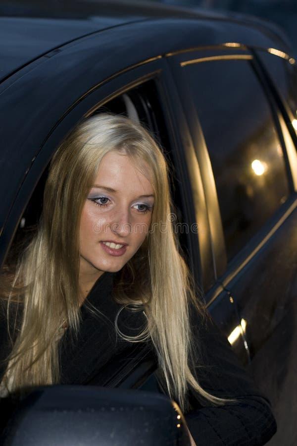 Vrouw die uit een autoraam leunt royalty-vrije stock afbeelding