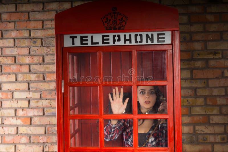 Vrouw die uit een telefooncel in verschrikking turen stock fotografie