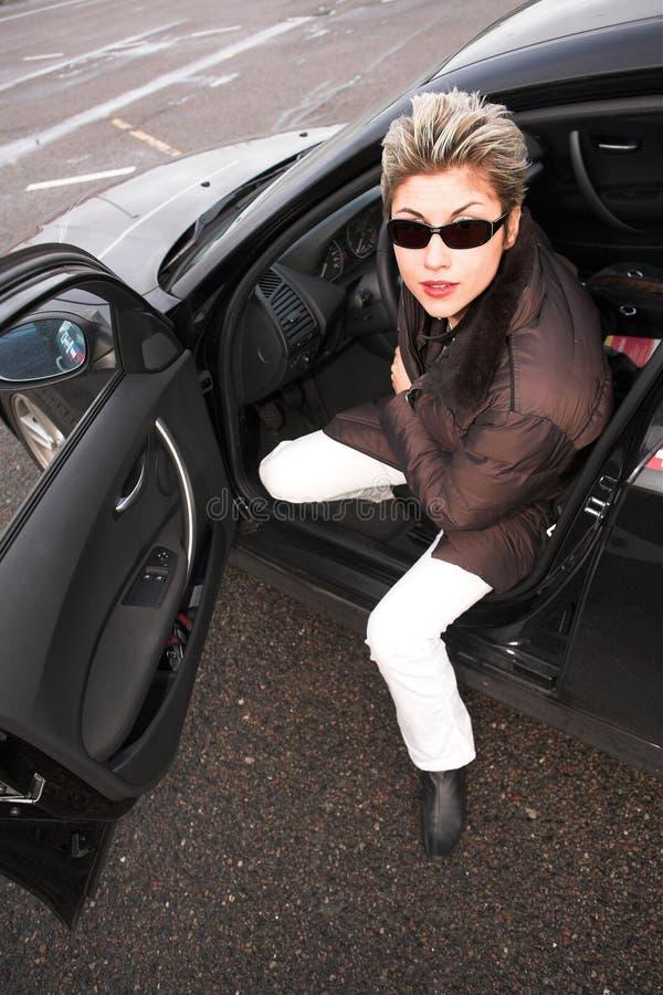 Vrouw die uit haar auto komt stock afbeelding