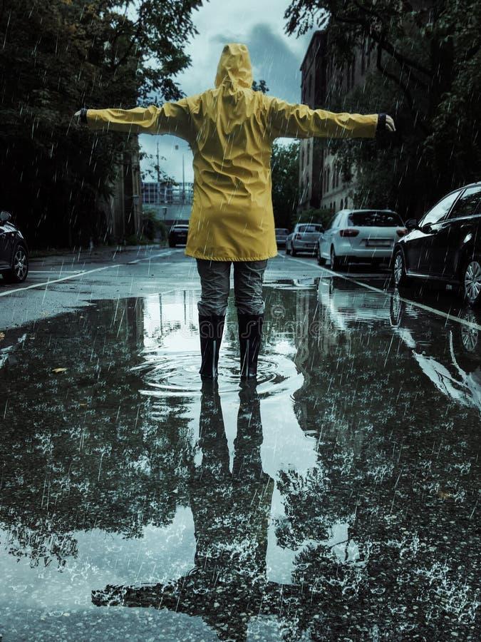 Vrouw die uit haar wapens op een regenachtige dag in de herfst bereiken stock fotografie