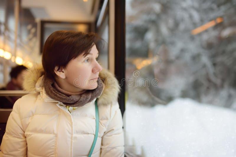 Vrouw die uit het venster van trein tijdens reis op tandradspoorweg/rekspoorweg kijken in de bergen van Alpen stock fotografie