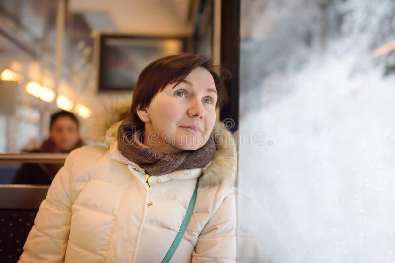 Vrouw die uit het venster van trein tijdens reis op tandradspoorweg/rekspoorweg kijken in de bergen van Alpen royalty-vrije stock foto's