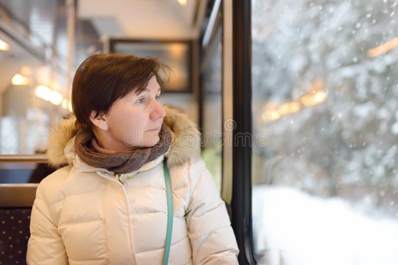 Vrouw die uit het venster van trein tijdens reis op tandradspoorweg/rekspoorweg kijken in de bergen van Alpen stock afbeeldingen
