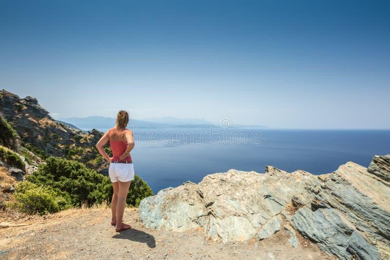 Vrouw die uit over Mediterrane kust van Cap Corse in Cor kijken stock foto