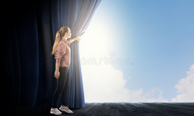 Vrouw die uit van gordijn kijken stock foto