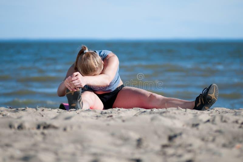 Vrouw die uitrekkende oefening op strand doet royalty-vrije stock fotografie