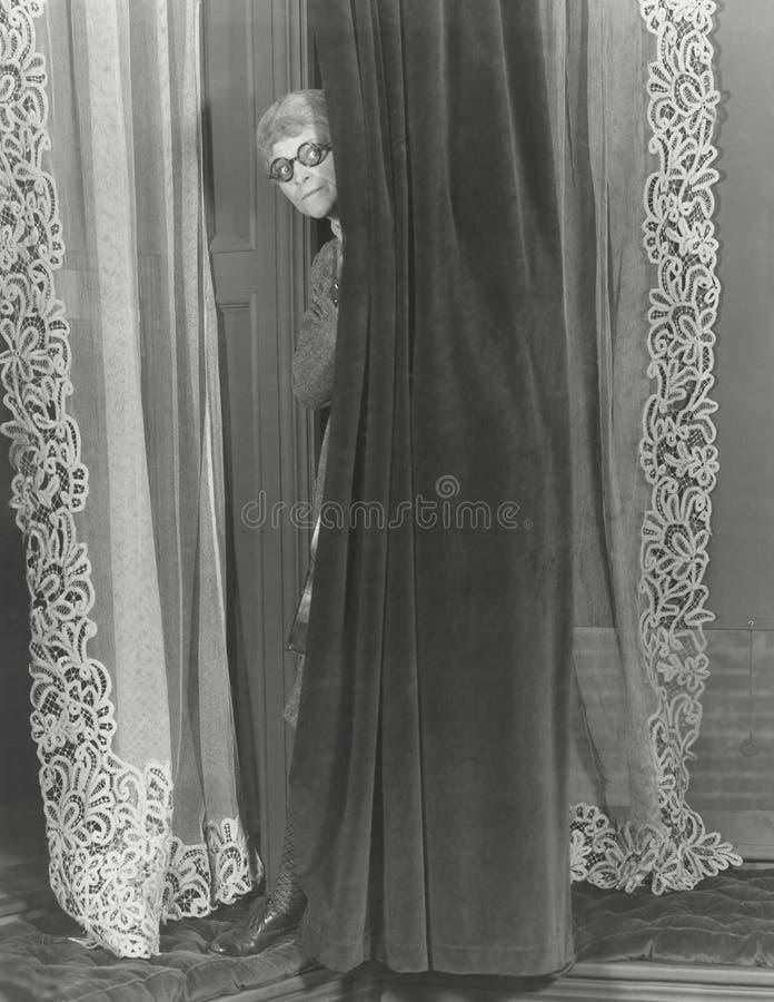 Vrouw die van achter gordijn afluisteren stock foto