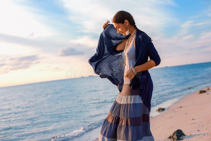 Vrouw die van Beuatiful de jonge boho op het strand bij zonsondergang lopen stock afbeelding