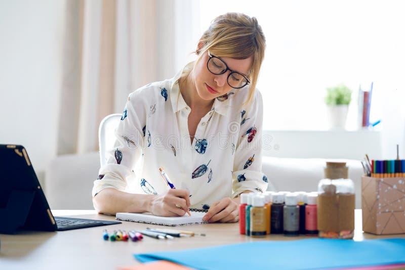 Vrouw die van de Pofessional de mooie jonge ontwerper nota's in notitieboekje nemen op het kantoor stock foto