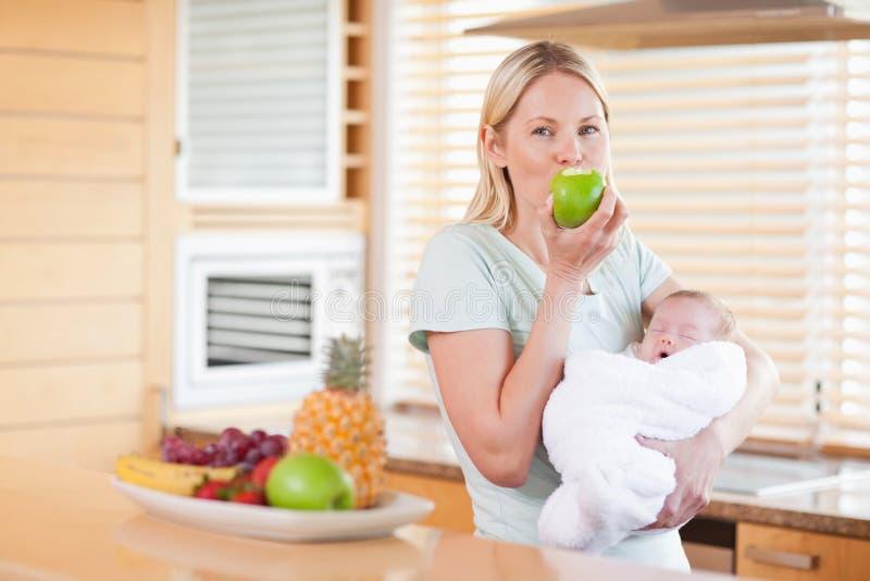 Vrouw die van een appel met haar baby op haar wapens geniet stock afbeeldingen