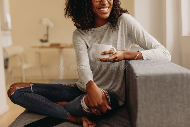 Vrouw die van een kop van koffiezitting thuis genieten stock foto