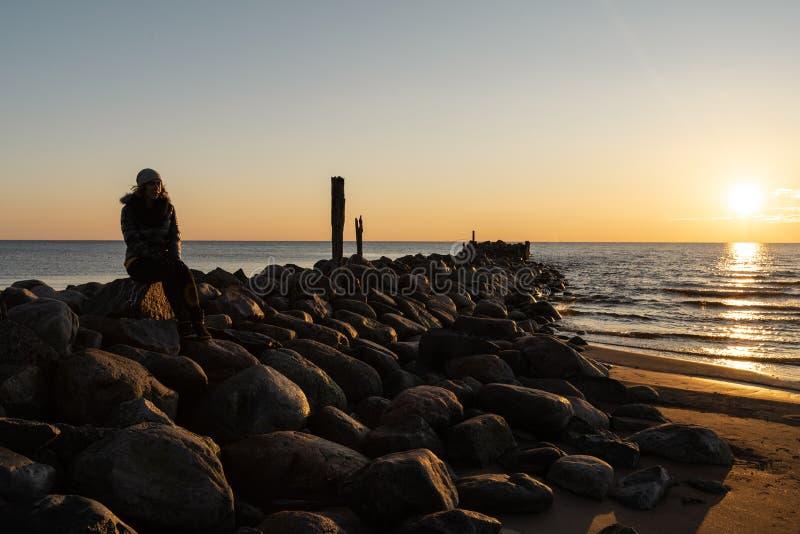 Vrouw die van een koude de Lentezonsondergang genieten bij een keistrand dichtbij de Oostzee stock afbeelding