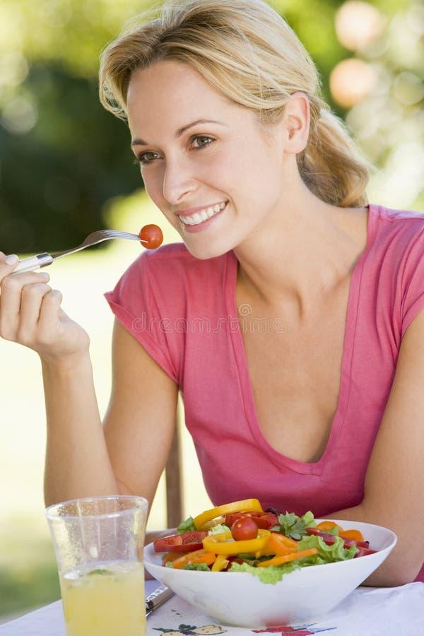 Vrouw die van een Salade in een Tuin geniet stock afbeeldingen