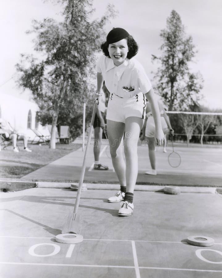 Vrouw die van een spel van sjoelbak genieten royalty-vrije stock foto's