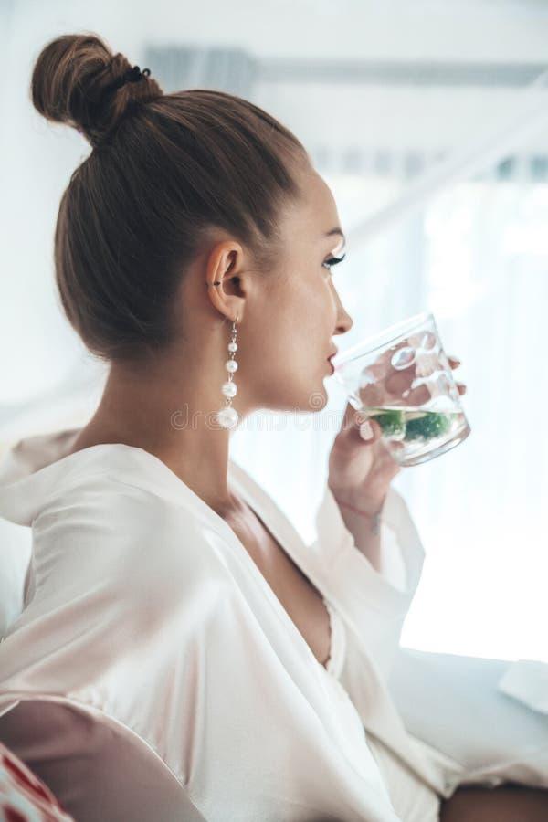 Vrouw die van een tropische die mojitococktail genieten met vers fruit op haar de zomervakantie wordt verfraaid stock foto's