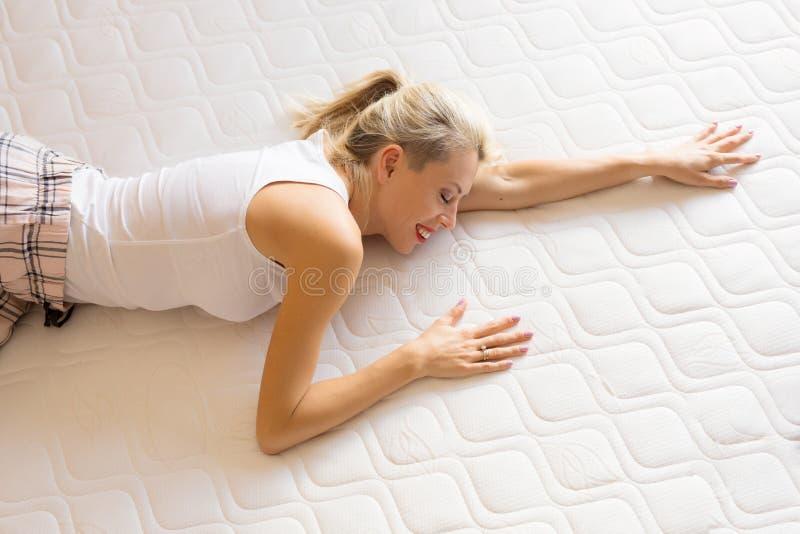 Vrouw die van haar nieuwe comfortabele matras genieten royalty-vrije stock foto