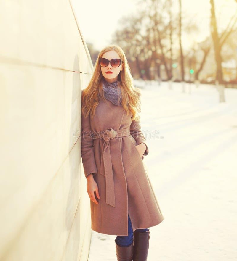 Vrouw die van het manier de mooie jonge blonde laagjasje en zonnebril in de winterstad dragen royalty-vrije stock foto