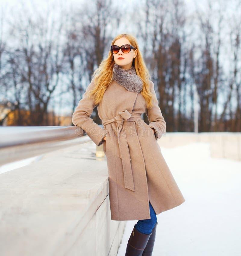 Vrouw die van het manier de mooie jonge blonde laagjasje en zonnebril in de winterstad dragen royalty-vrije stock afbeelding