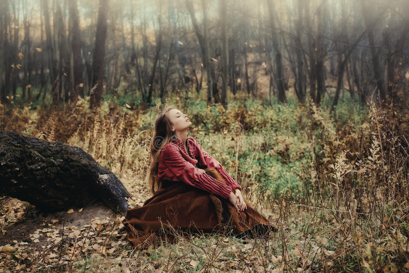 Vrouw die van het in openlucht binnen de herfstbos genieten stock foto's