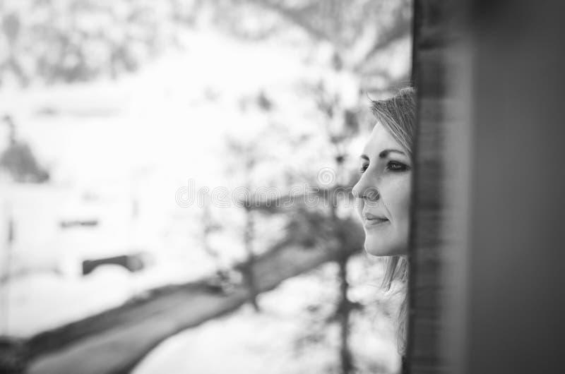 Vrouw die van het venster kijkt royalty-vrije stock afbeeldingen