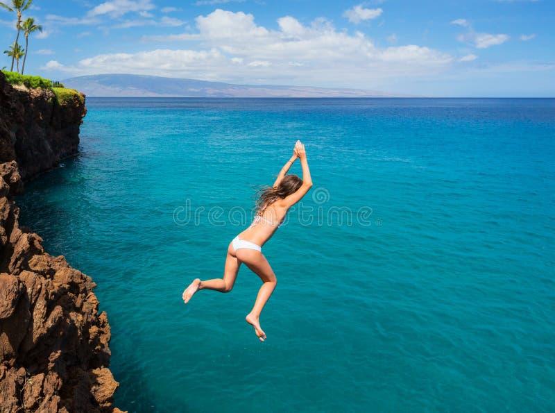 Vrouw die van klip in de oceaan springen royalty-vrije stock afbeeldingen