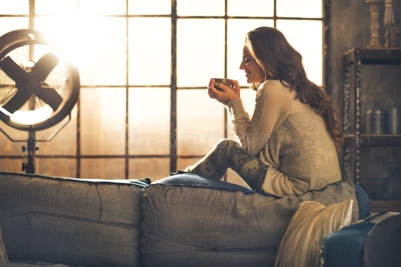 Vrouw die van kop van hete drank in flat genieten stock foto