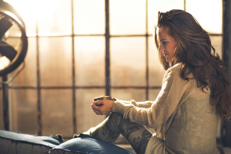 Vrouw die van kop van koffie in zolderflat genieten royalty-vrije stock afbeelding