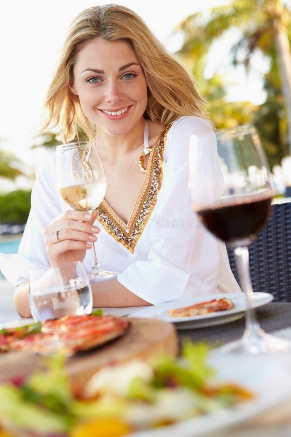 Vrouw die van Maaltijd in Openluchtrestaurant genieten stock afbeelding