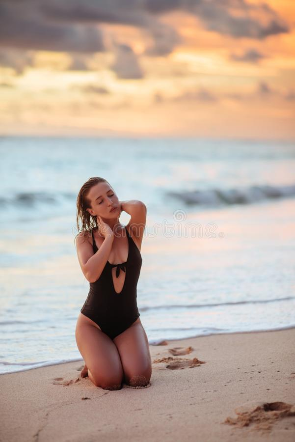 Vrouw die van mooie zonsondergang op het strand genieten royalty-vrije stock afbeeldingen