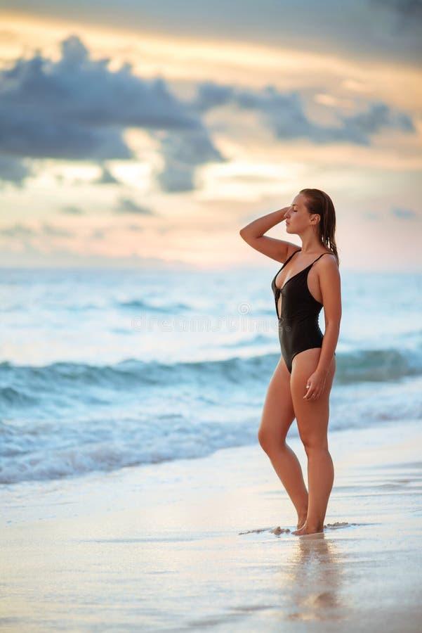 Vrouw die van mooie zonsondergang op het strand genieten royalty-vrije stock afbeelding