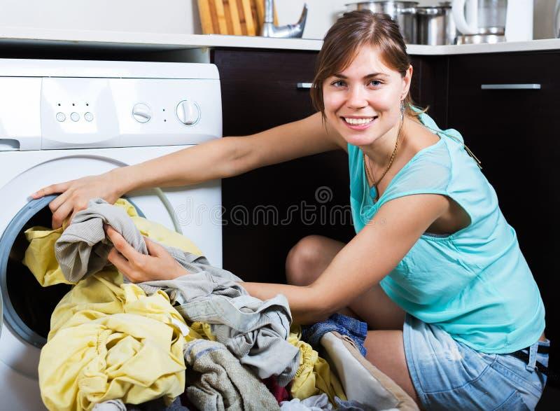 Vrouw die van schone kleren na wasserij genieten stock foto's