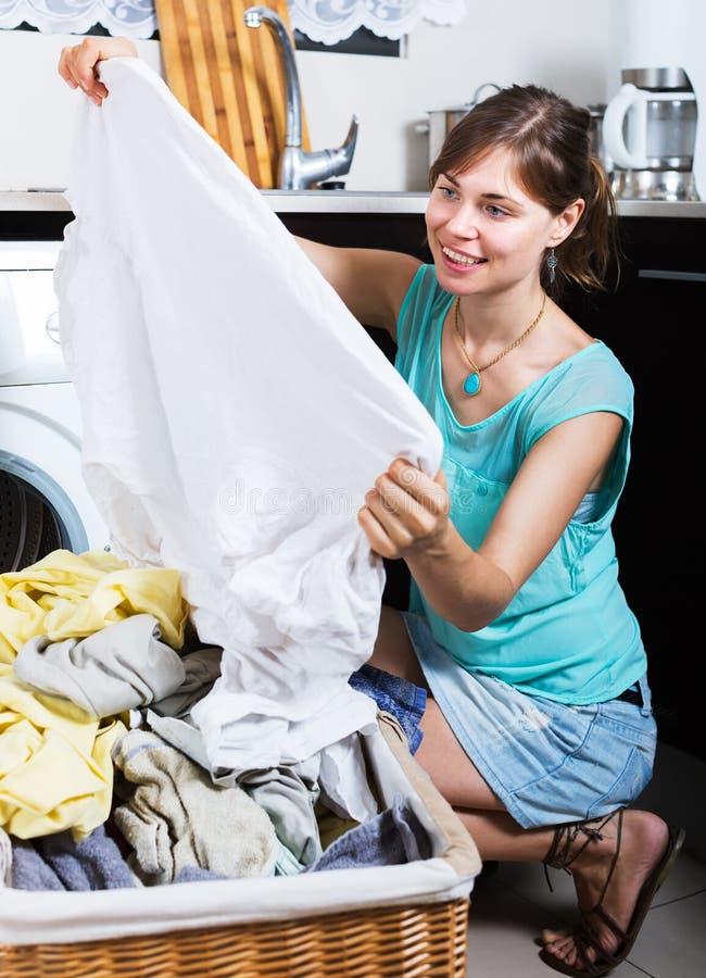 Vrouw die van schone kleren na wasserij genieten stock afbeelding