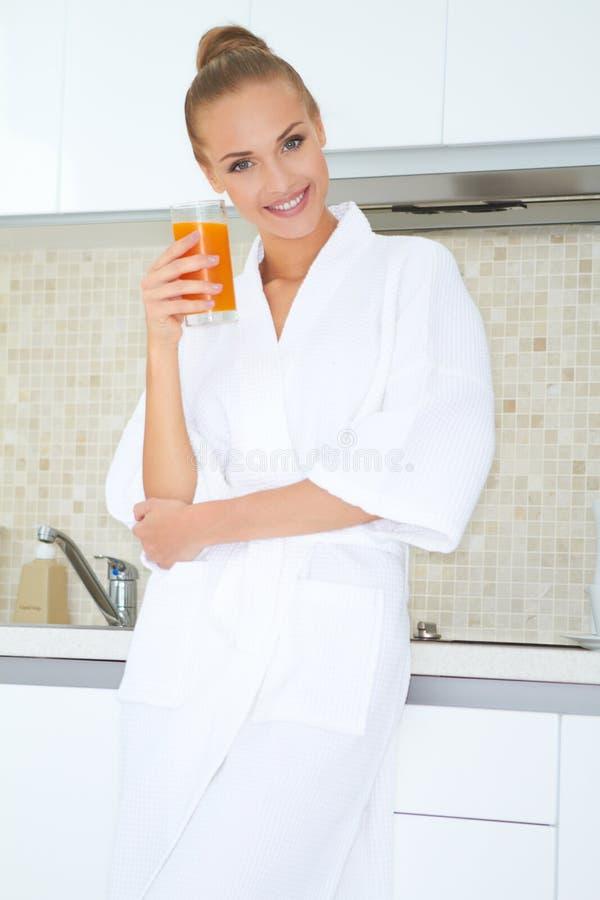 Vrouw die van vers jus d'orange voor ontbijt genieten stock foto's