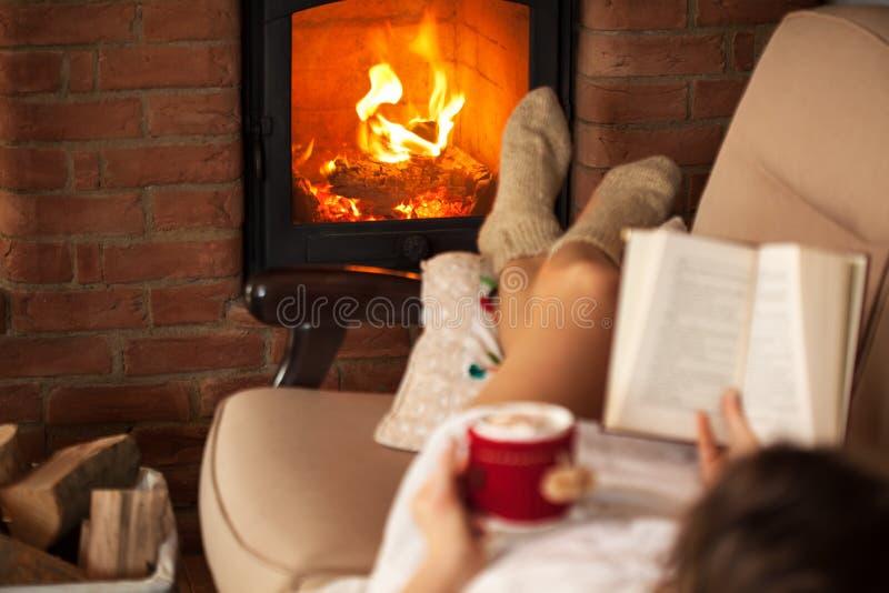 Vrouw die van vrije tijd genieten door de brand die - een boek lezen stock afbeelding