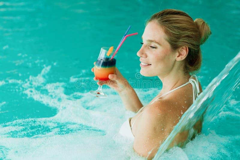 Vrouw die van watergeneeskunde en cocktail genieten stock foto's