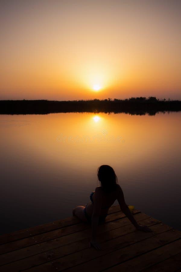 Vrouw die van zonsondergang op het houten dok genieten royalty-vrije stock afbeelding