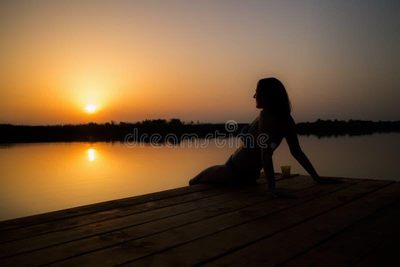 Vrouw die van zonsondergang op het houten dok genieten stock afbeelding