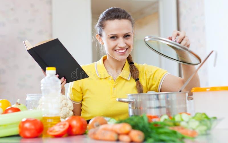 Vrouw die vegetarisch voedsel met kookboek koken royalty-vrije stock afbeeldingen