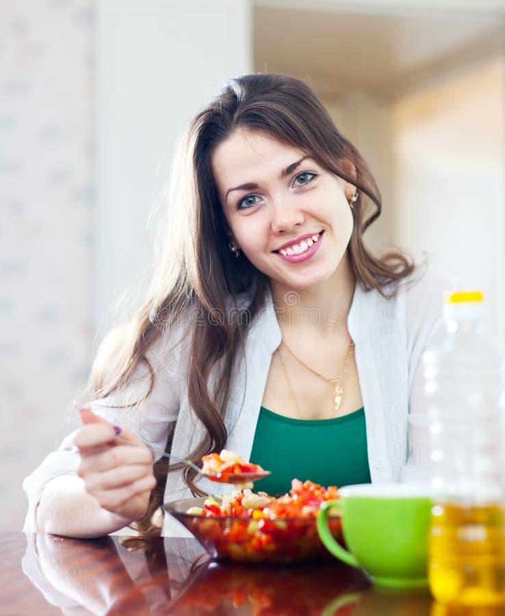Vrouw die veggie salade met lepel eten stock foto's