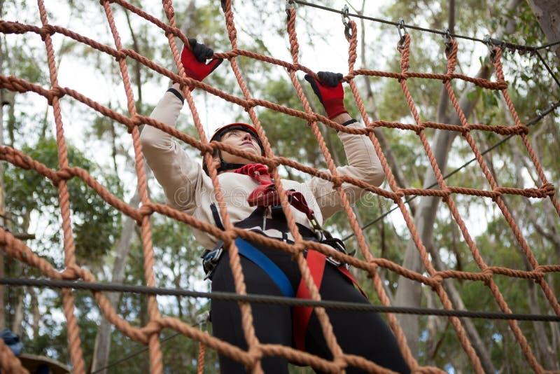 Vrouw die veiligheidshelm dragen die op een kabelomheining beklimmen royalty-vrije stock fotografie