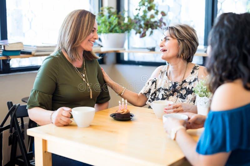 Vrouw die verjaardagswensen van vrienden ontvangen bij koffie royalty-vrije stock foto