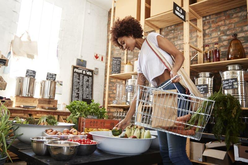 Vrouw die Vers Fruit en Groenten in Duurzame Plastic Vrije Kruidenierswinkelopslag kopen stock afbeelding