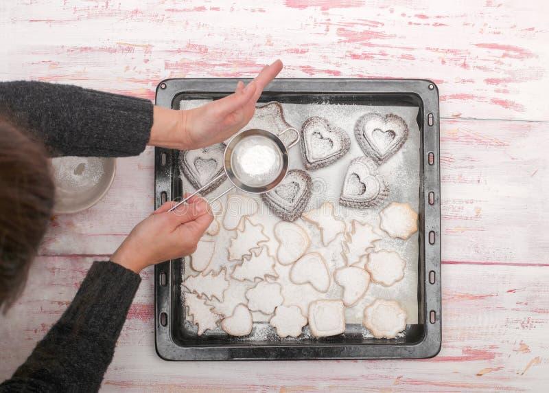 Vrouw die vers gebakken traditionele nieuwe jaarkoekjes op RT beëindigen stock fotografie