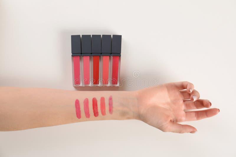 Vrouw die verschillende lippenstiften op witte achtergrond testen stock fotografie
