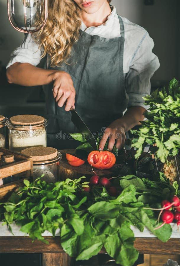 Vrouw die verse rijpe tomaten op concrete keukenteller snijden royalty-vrije stock fotografie