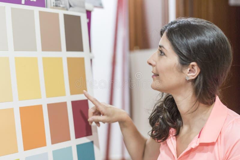 Vrouw die in verven en de kleurensteekproeven van de ambachtenopslag kijken royalty-vrije stock foto